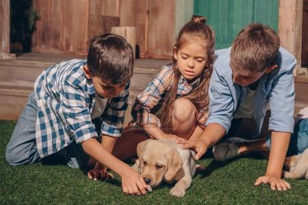 kids with cute labrador puppy