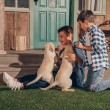 Little boys playing with cute labrador puppies tog...