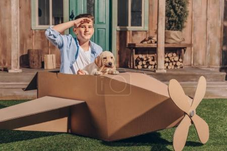 Boy with puppy in cardboard airplane