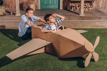 boys playing with cardboard airplane