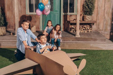 Photo for Girls sitting on porch while boys playing with cardboard airplane - Royalty Free Image