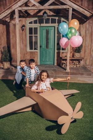 Photo pour Afro-américaine fille avec des ballons et des garçons jouer avec avion en carton ensemble - image libre de droit