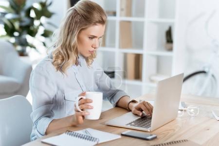Photo pour Vue latérale de la jeune femme d'affaires avec tasse de café à la main tapant sur ordinateur portable dans le bureau - image libre de droit