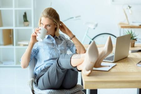 Photo for Businesswoman drinking coffee while sitting at workplace with laptop in office - Royalty Free Image