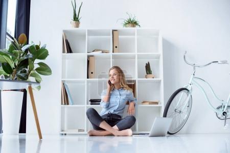 Photo pour Femme d'affaires assise sur le sol avec ordinateur portable et parlant sur smartphone dans le bureau - image libre de droit