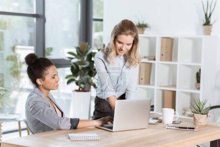 Photo pour Femmes d'affaires multiethniques discutant d'un nouveau projet d'entreprise pendant qu'elles sont au bureau - image libre de droit