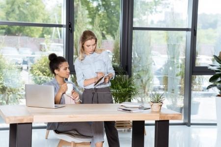 Photo pour Femmes d'affaires multiethniques discutant affaires nouvelles du projet tout en étant assis au milieu de travail au bureau - image libre de droit
