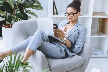 african american businesswoman using smartphone