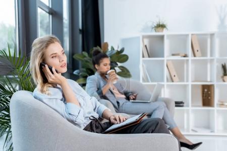 Photo pour Femme d'affaires parlant sur smartphone tandis que le collègue afro-américain buvant du café travaillant sur un ordinateur portable à proximité - image libre de droit