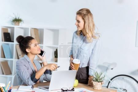 Photo pour Afro-américaine femme d'affaires parlant sur smartphone tandis que son collègue avec du café pour aller debout près de - image libre de droit