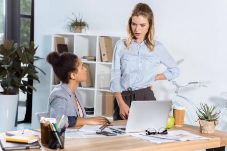 Photo pour Femmes d'affaires multiethniques travaillant sur ordinateur portable tout en discutant du nouveau plan d'affaires sur le lieu de travail au bureau - image libre de droit