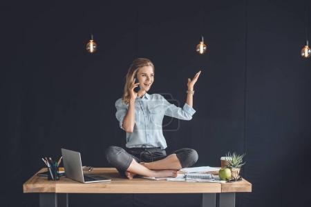 Photo pour Femme d'affaires joyeuse assise en position lotus et parlant sur smartphone au bureau - image libre de droit