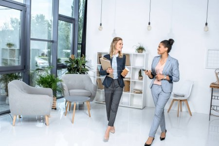 Photo for Multicultural businesswomen having conversation while walking in office - Royalty Free Image