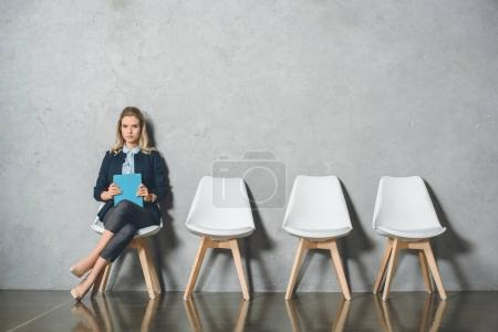 Photo for Confident businesswoman with clipboard sitting on chair and waiting for interview - Royalty Free Image