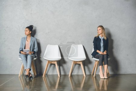 Photo for Young multicultural businesswomen sitting on chairs and waiting for job interview - Royalty Free Image