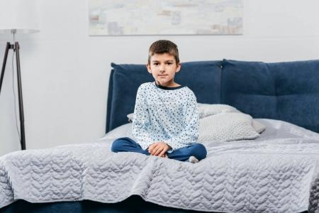little boy sitting on bed