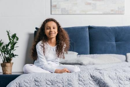 african american girl sitting on bed