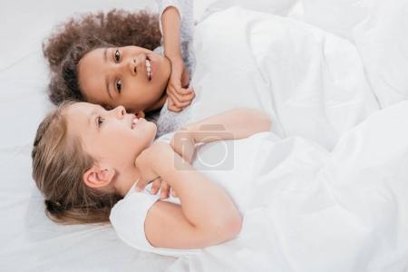 multicultural girls lying in bed