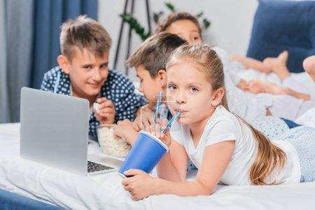 Photo pour Petite fille boire soda tandis que les amis en utilisant un ordinateur portable à la maison - image libre de droit