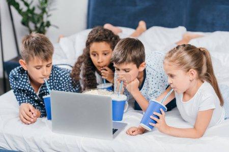 Photo pour Enfants multiculturels boire de la soude et regarder un film à la maison ensemble - image libre de droit