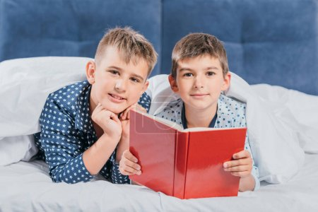 Boys reading book together