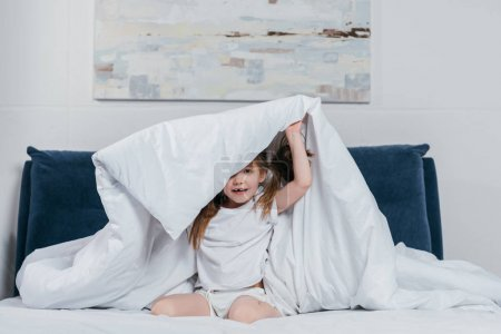 girl hiding under blanket