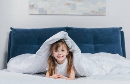 girl hiding under blanket