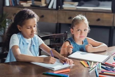 Photo for Portrait of multicultural focused girls drawing pictures while sitting at table together - Royalty Free Image