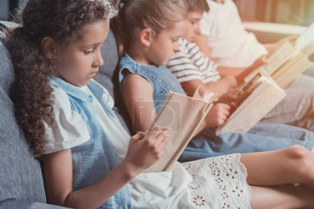 Photo for Multicultural group of focused children reading books while sitting on sofa at home together - Royalty Free Image