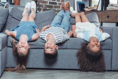 multiethnic children lying on sofa