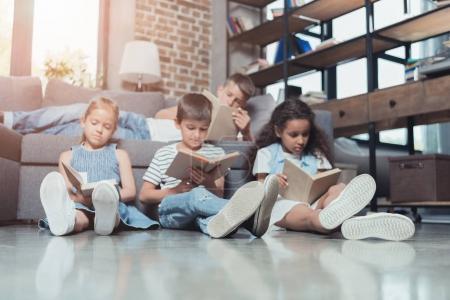 Photo pour Groupe multiculturel d'enfants concentrés lisant des livres à la maison ensemble - image libre de droit