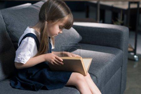 Photo pour Vue latérale de la petite fille assise sur le canapé et le livre de lecture à la maison - image libre de droit