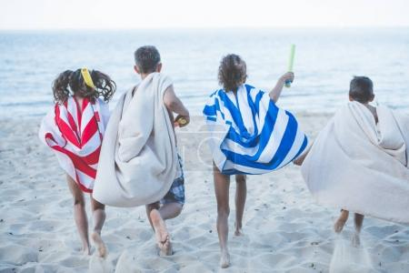 children with towels running on beach