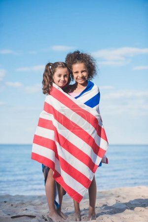 Photo for Multicultural smiling girls in towel standing together on beach - Royalty Free Image