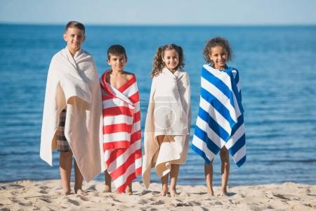 Photo for Multicultural children in colorful towels standing at seaside and looking at camera - Royalty Free Image