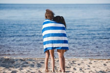 Girls in towel standing on beach