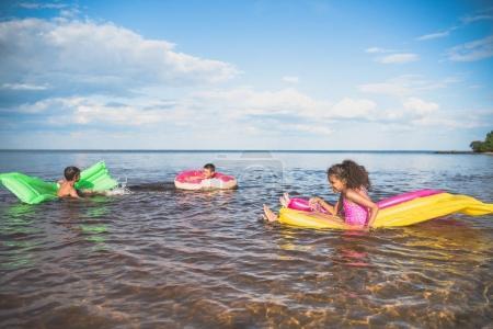 Foto de Multiétnicos niños nadando en colchones inflables coloridos en el mar juntos - Imagen libre de derechos