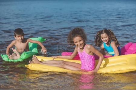Multiethnic children on inflatable mattresses