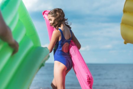 Photo for Side view of little girl holding inflatable mattress while walking on beach - Royalty Free Image