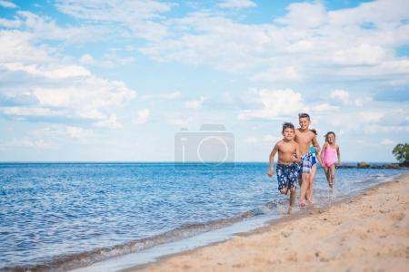 multiethnic children running on beach