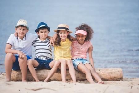 Photo for Multiethnic children hugging each other while sitting on wooden trunk at seaside - Royalty Free Image