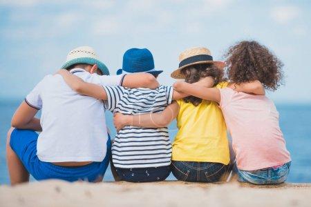 Photo pour Vue arrière des garçons et des filles assis ensemble sur un coffre en bois au bord de la mer - image libre de droit