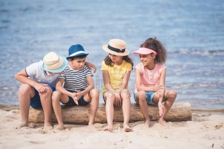 Photo for Multiethnic little children sitting on wooden trunk at seaside - Royalty Free Image