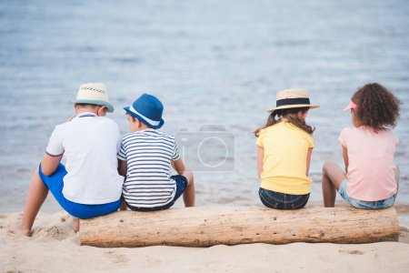 children sitting at seaside