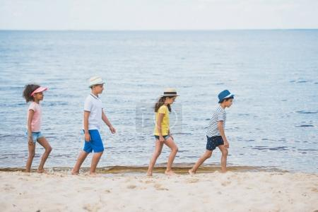 multicultural kids walking on beach