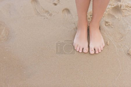 Photo for Cropped view of child standing on sandy beach alone - Royalty Free Image