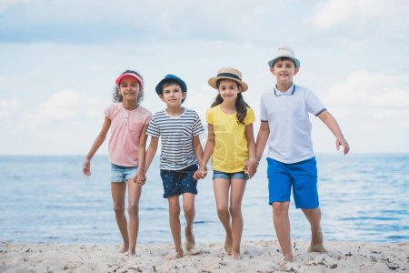 Photo for Multicultural kids holding hands while walking on beach together - Royalty Free Image