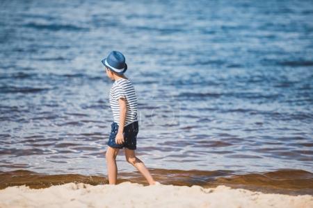 boy walking on sandy beach