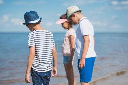 Multicultural children standing at seaside