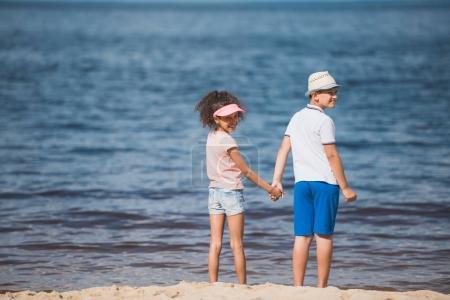 multiethnic children standing at seaside